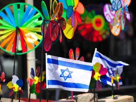 Two small Israel flags stands between colorful windmill toys in gift shop photo