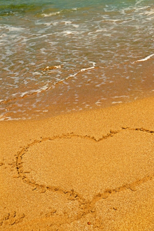 Heart shape symbol drawn in sand on a beach Stock Photo - 14254658