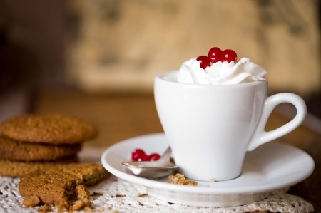 Crumbling oat cookies biscuits with hot coffee and whipped cream with cranberries on top  Shallow DOF Stock Photo