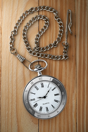 Photo of silver vintage pocket watch with chain on wooden background photo