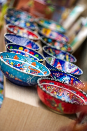 Small beautiful arabic colorful pottery bowls arranged in a row at the street market of Antalya, Turkey