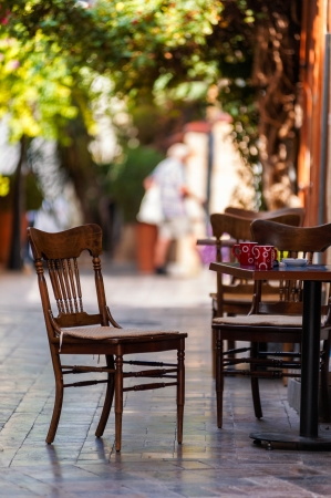 Street view of a empty coffee terrace with tables and chairs in old town of Antalya, Turkey. Small depth of field.