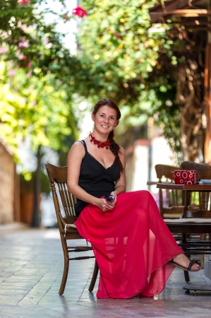 Cheerful beautiful woman in red dress sitting at a sidewalk cafe Stock Photo - 17629777