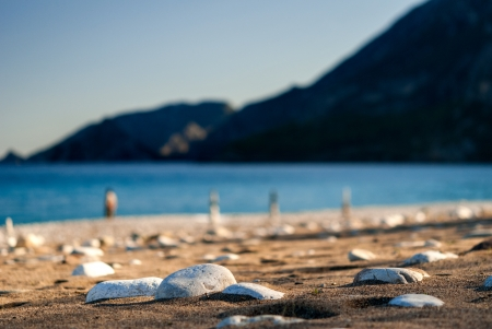 Stones on the sand beach close-up  Background of blurry mountain and sea Stock Photo - 17915966