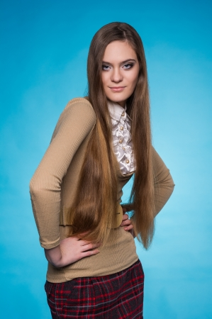 Beautiful teen girl with long straight hair, posing on blue background