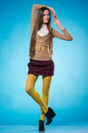 Beautiful teen girl with long straight hair, posing on blue background photo