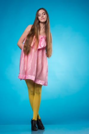 Young teen girl in a pink dress posing with closed eyes over blue background Stock Photo - 19359616