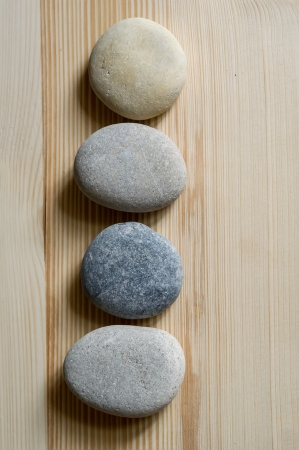 Spa zen stones are aligned in a line on light wood background