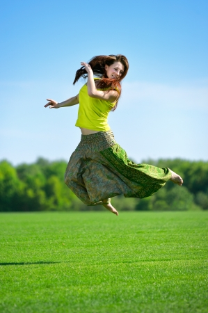 Young beautiful woman jumpimg on a green meadow photo