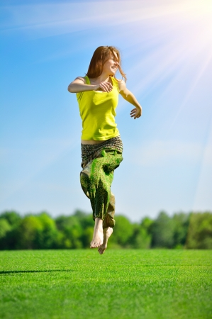 Young beautiful woman running on a green meadow photo