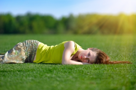 Young beautiful woman lying on a green meadow, sun rays beaming photo