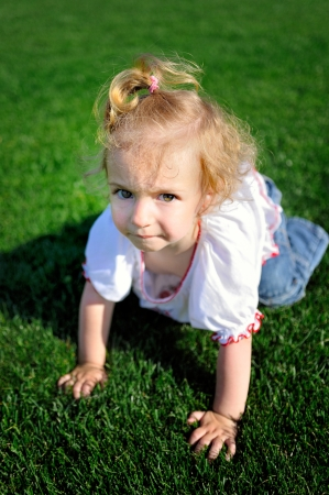 Cute little girl crawling on the green grass in the park Stock Photo - 19637363