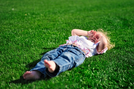 Cute little girl laying on the green grass in the park photo