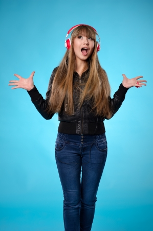 Rock style teen girl listening to music with big red headphones. Isolated over blue background photo