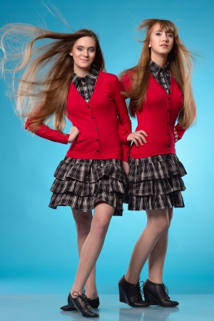 Two teen schoolgirls stand side by side over studio blue background. Wind blows on hairs photo