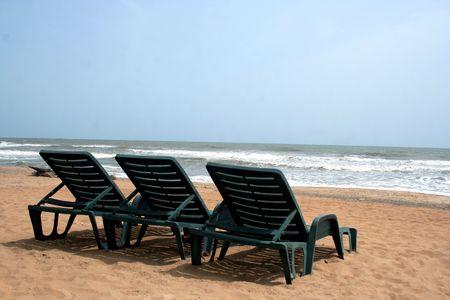 deckchair on a tropical beach with sky and white sand