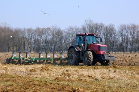 Tractor ploegen het nieuwe veld in het voorjaar
