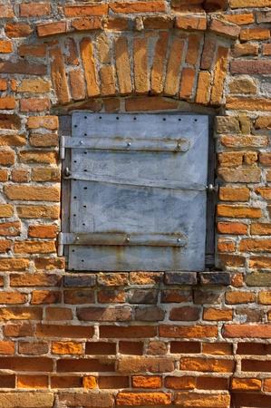 Oude bakstenen muur met gesloten stalen deur Stockfoto
