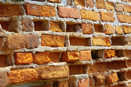Old front wall with weather-beaten bricks Stock Photo