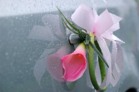 Flower decoration on silver wedding car with rain drops