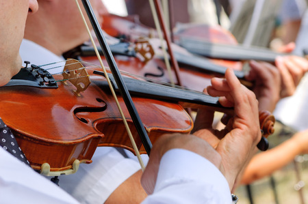 Musicians playing on violins in the street orchestra Stock Photo