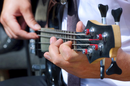 Musician playing bass guitar focus on left hand Stock Photo