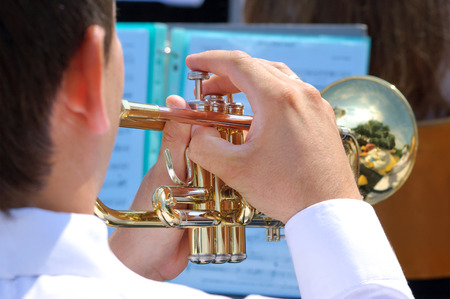 Musician playing on golden trumpet in street orchestra