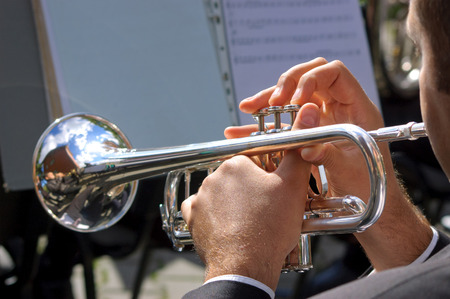 Musician playing on silver trumpet in street orchestra Stock Photo