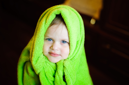 0 6: the girl who opened the head green fleece blanket, standing inside a dark room Stock Photo
