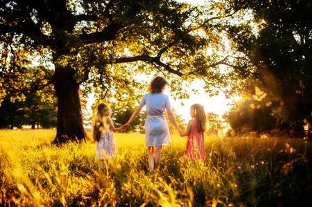 Mother and daughters hold hands on sunset in the forest 写真素材