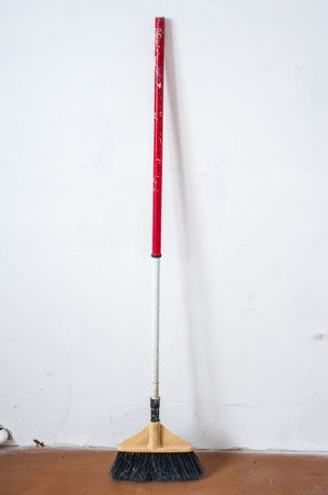 Close up of red black broom on white background. Cleanliness concept
