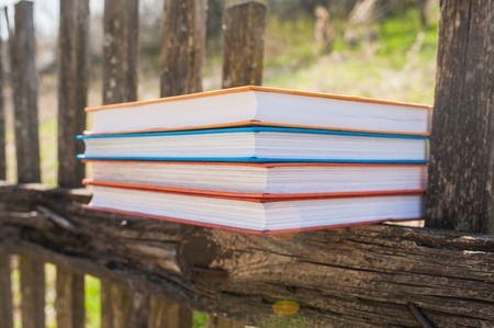 Stack of books in color covers in nature. A stack of books in color covers on a wooden fence. The concept of education, science Imagens