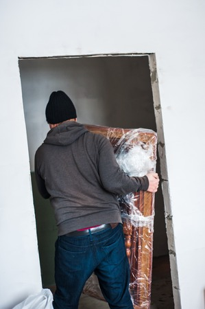 The worker takes out old things from the repaired premises.