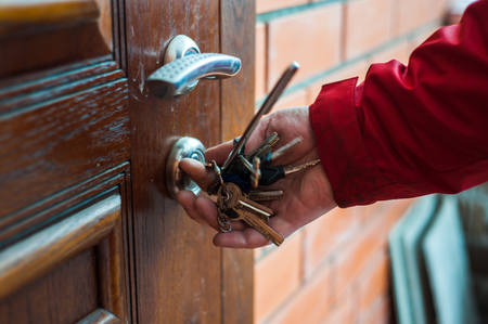 Close up person hand opens the wooden door using bunch of keys Archivio Fotografico