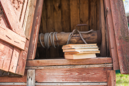 A stack of vintage books lie on a wooden old well. The concept of education, science Stock Photo