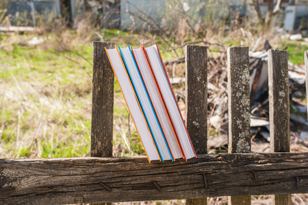 Stack of books in color covers in nature. A stack of books in color covers on a wooden fence. The concept of education, science 写真素材