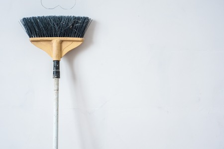 Close up of red black broom on white background. Cleanliness concept. Copy space. Stock Photo