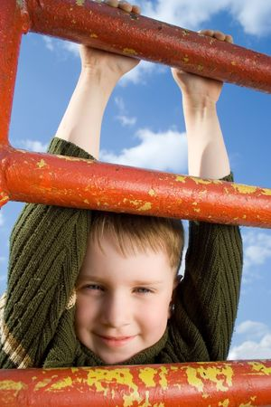 Boy hanging on the ladder