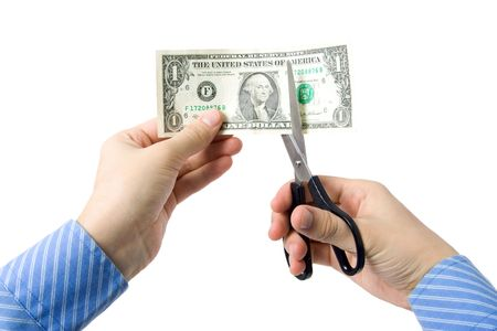 Hand with scissors, cutting one dollar bill photo