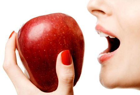 Closeup of a woman biting a red apple