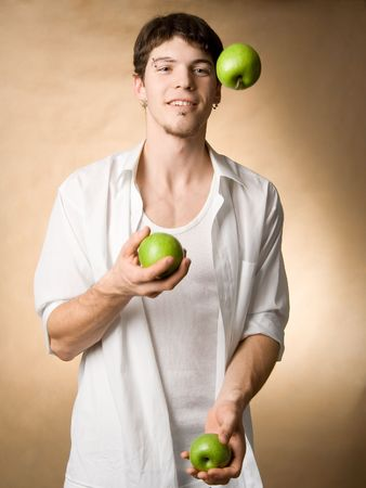 A young man juggling with green apples(apples and hand blured in motion) Stock Photo