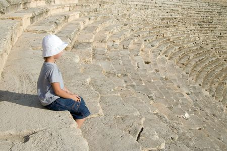 A small boy sitting in an amphitheatre photo