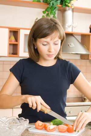 A young woman preparing salad in the kitchen Stock Photo