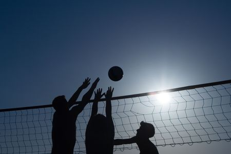 Silhouettes of 3 men, playing beach volleyball Stock Photo - 829250