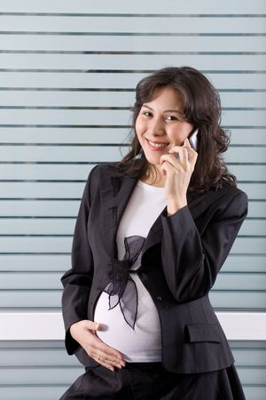Pregnant woman calling on the phone in office photo