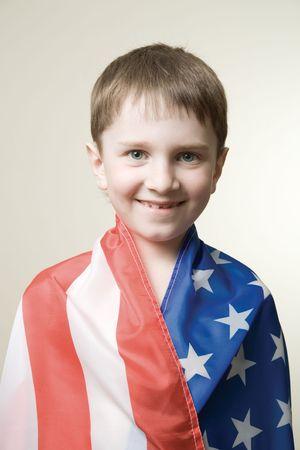 A happy boy wraped in american flag photo