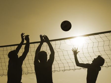 Silhouettes of three men playing beach volleyball,  Stock Photo