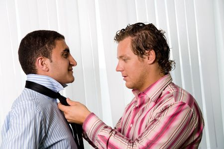 A homosexual couple, man helping with tie