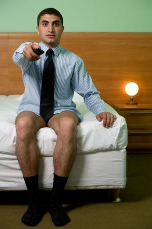 A man without pants watching tv in hotel photo