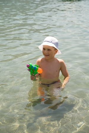 A boy with water pistol in the water photo